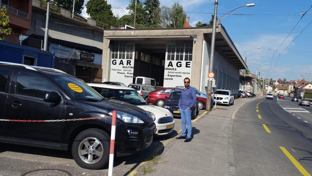Al Hasheme Arkan devant son garage au travail. Photo: Haider, membre de la rédaction neuchâteloise de Voix d'Exils.